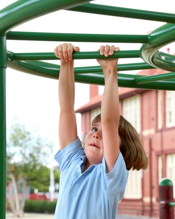 girl playing on monkey bars - school playground activities