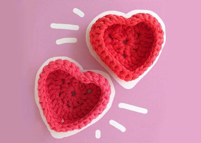 2 crochet heart shaped baskets on violet background