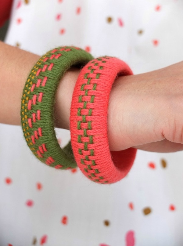 2 woven yarn bangles (pink and green) being worn on wrist