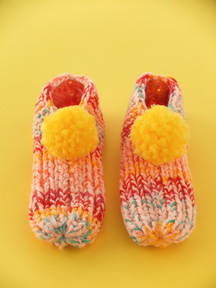 Finished knitted slippers with yellow pom poms