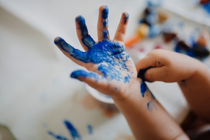 Child's hand with blue paint on palm and fingers