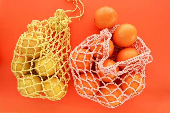 Crochet net bag holding ornages and lemons