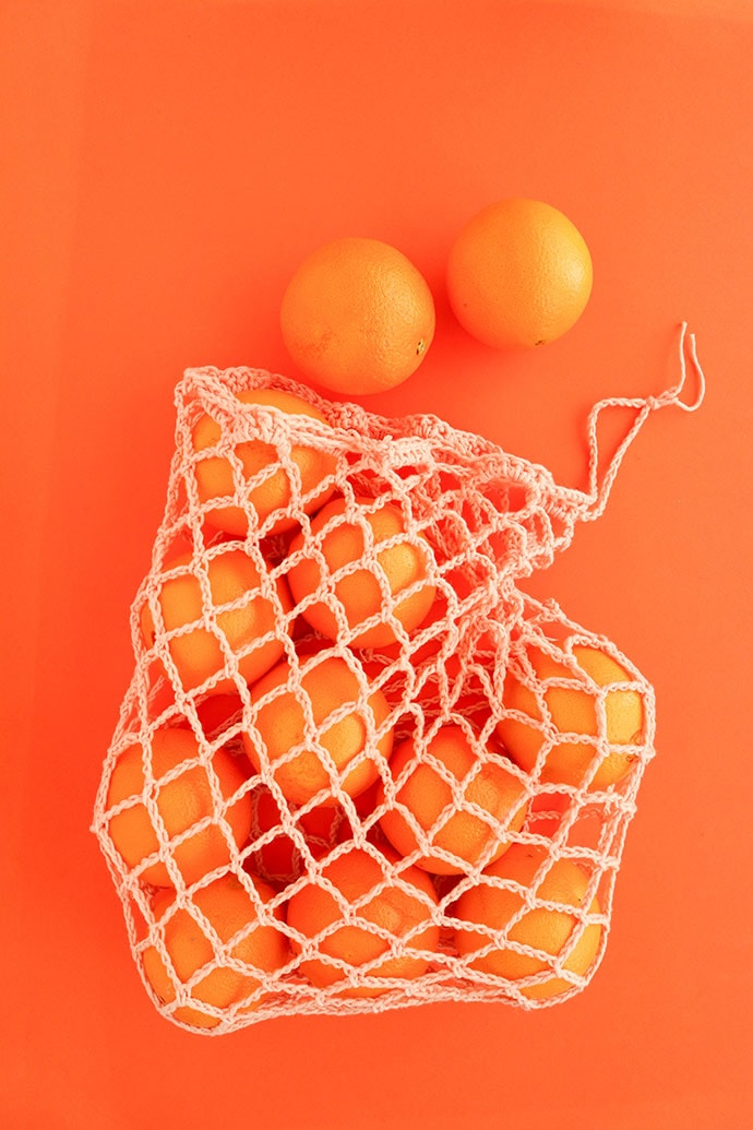 produce bag crochet pattern - Orange bag holding oranges on an orange background