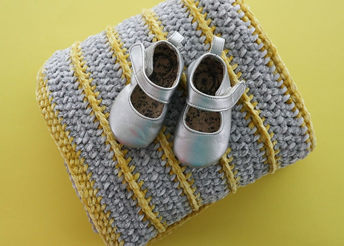 blanket with grey baby shoes on top