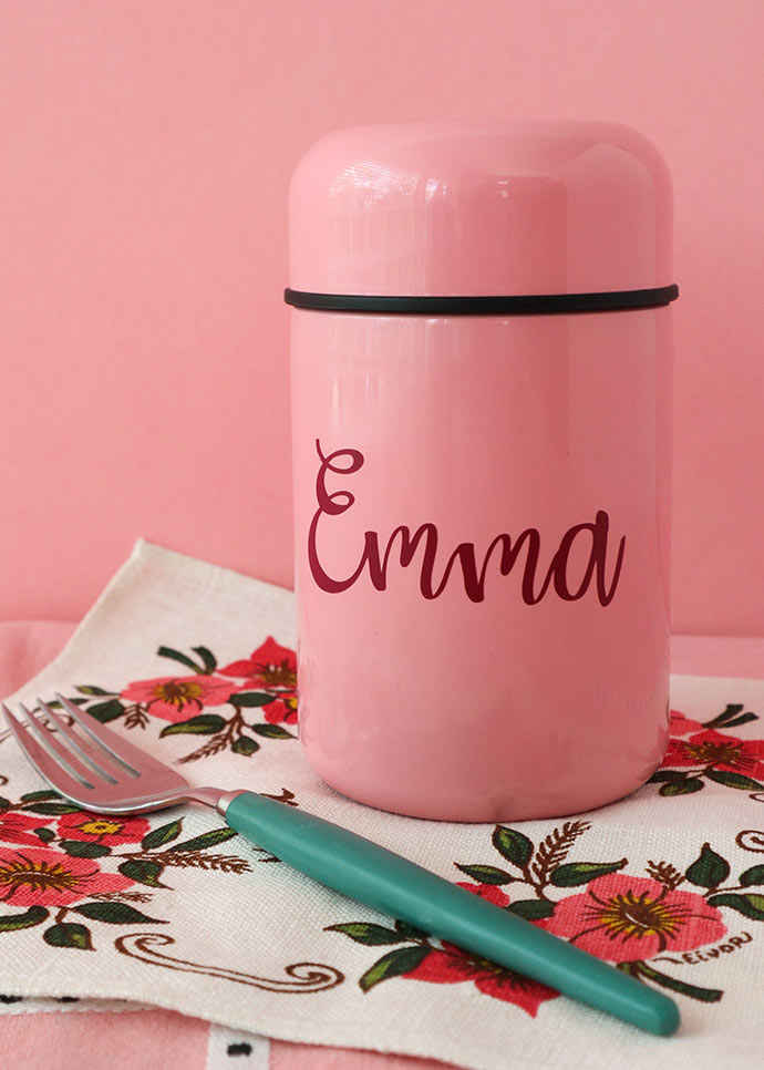 Pink thermos container on floral napkin