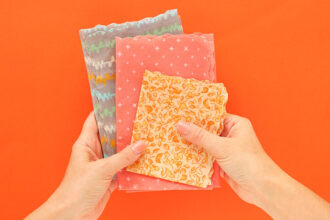 How to make beeswax wraps - hands holding 3 fabric wax wraps