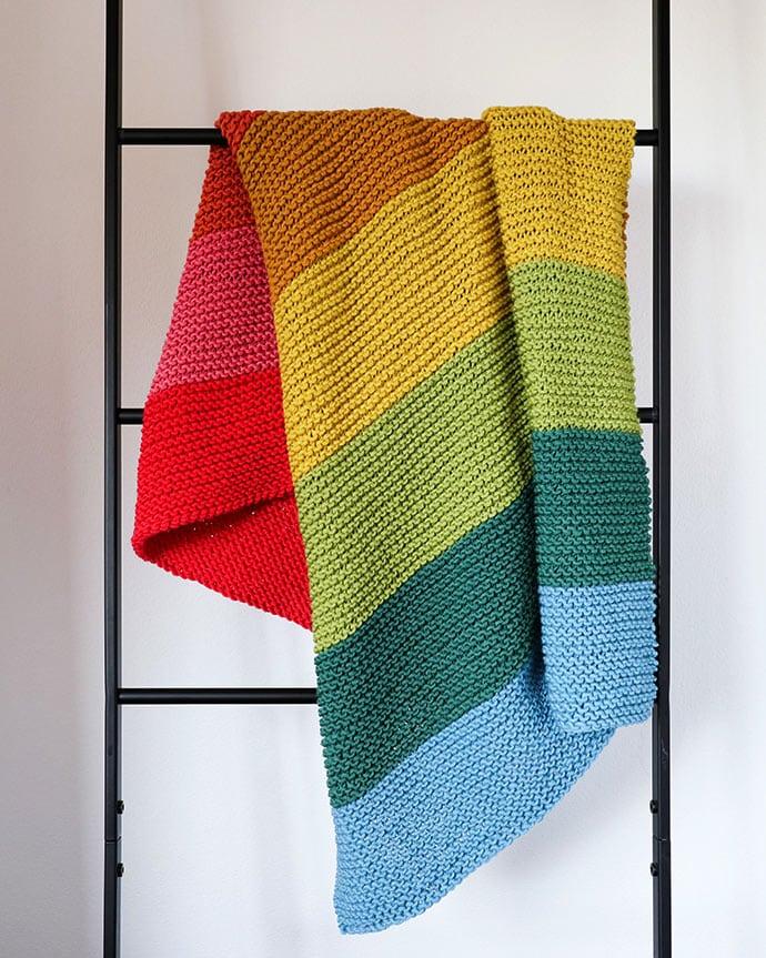 Rainbow blanket draped on ladder - Rainbow baby blanket knitting pattern - mypoppet.com.au