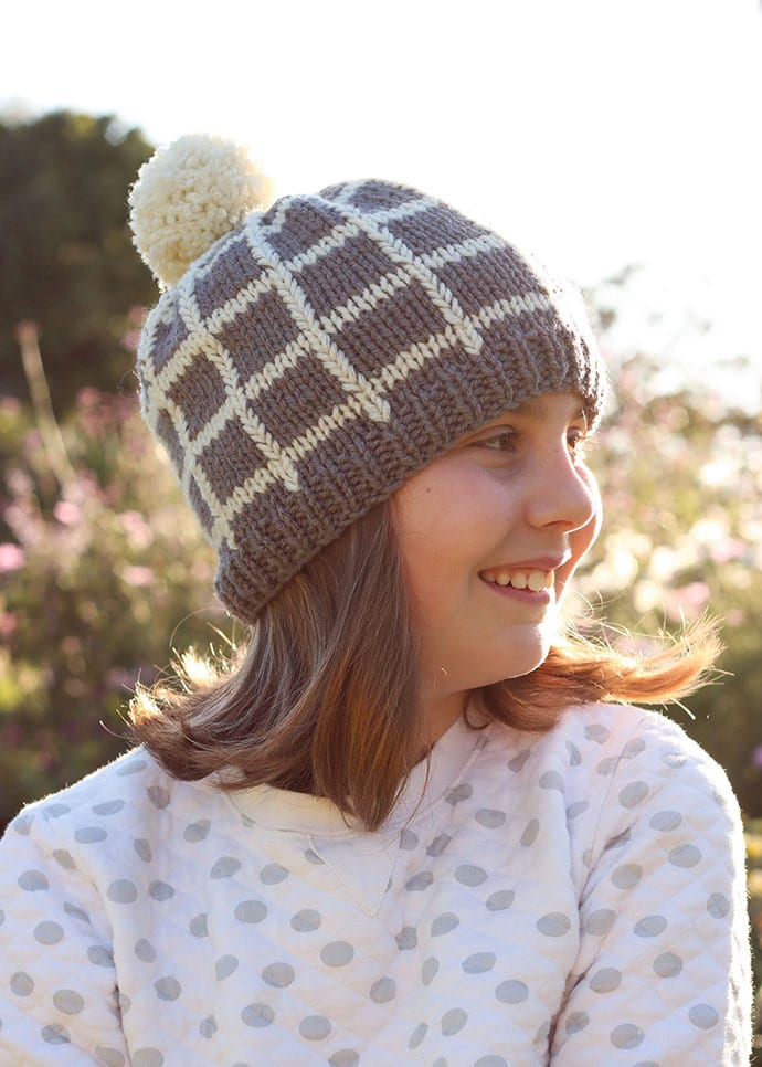 Grid Beanie knitted hat pattern. Girl wearing hat with pom pom