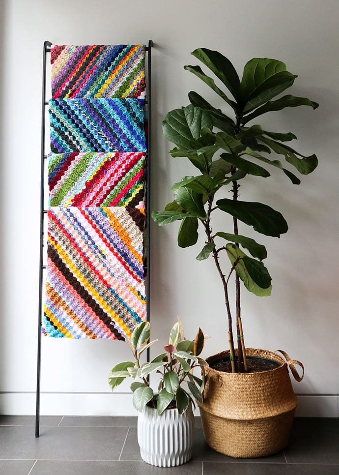 Crochet blankets hanging next to potted plants