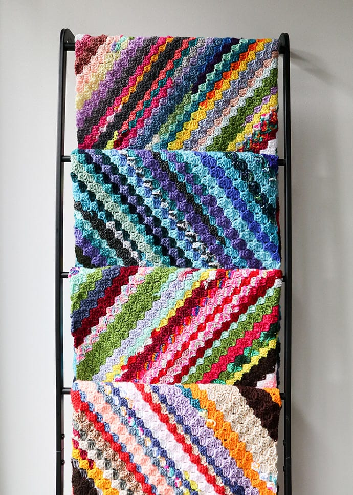 striped crochet blankets on a ladder - corner to corner crochet