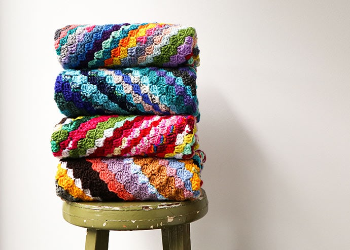 pile of crochet blankets on a stool
