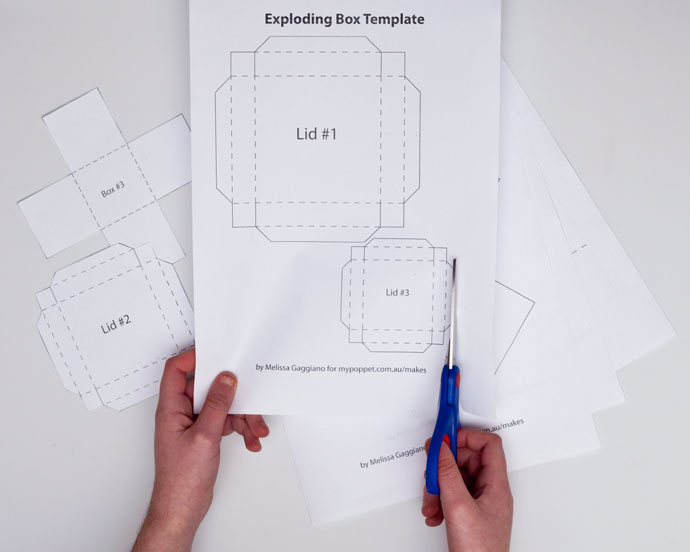 DIY Papercraft Exploding Box template - hands with scissors cutting paper