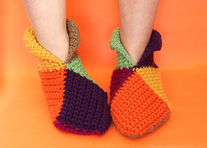 harlequin slippers - feet wearing crochet slippers on ornage background