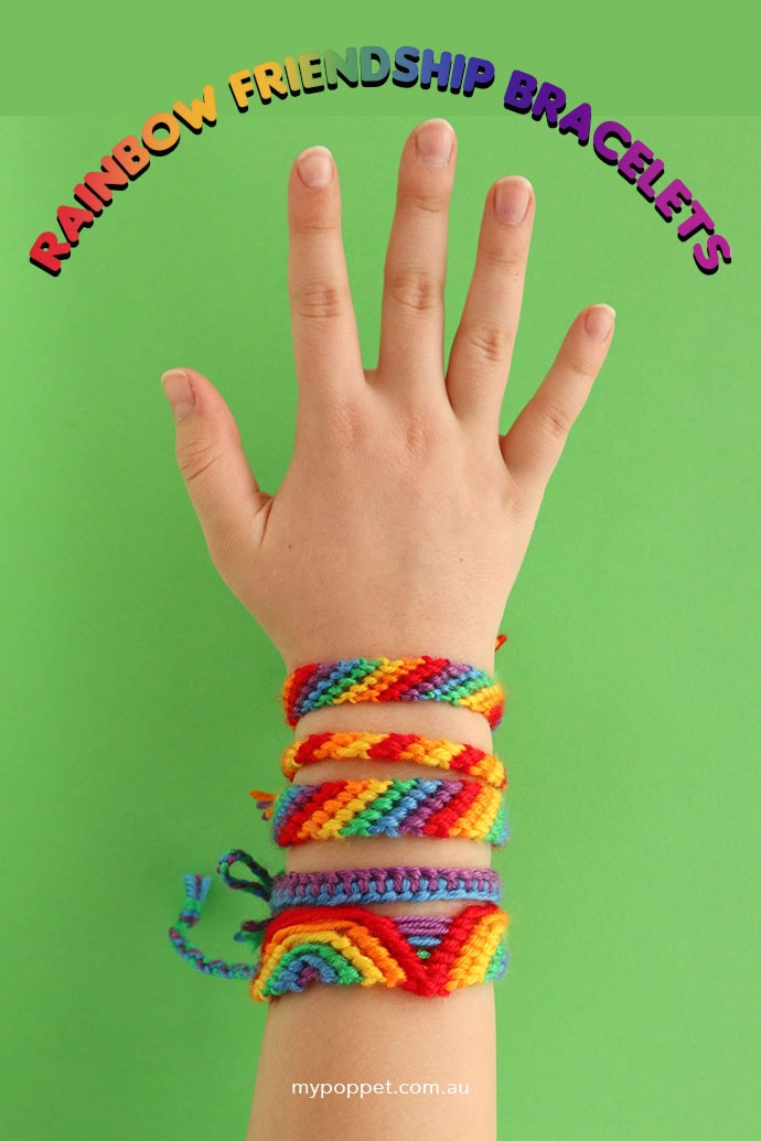 Girls hand wearing several rainbow hued friendship bracelets on green background