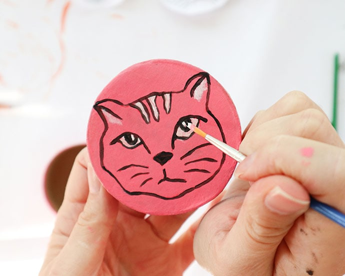 Painting a cat face on round orange box