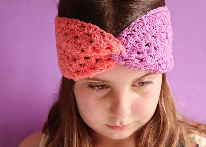 Girl wearing a crochet headband - colour blocked granny square headband
