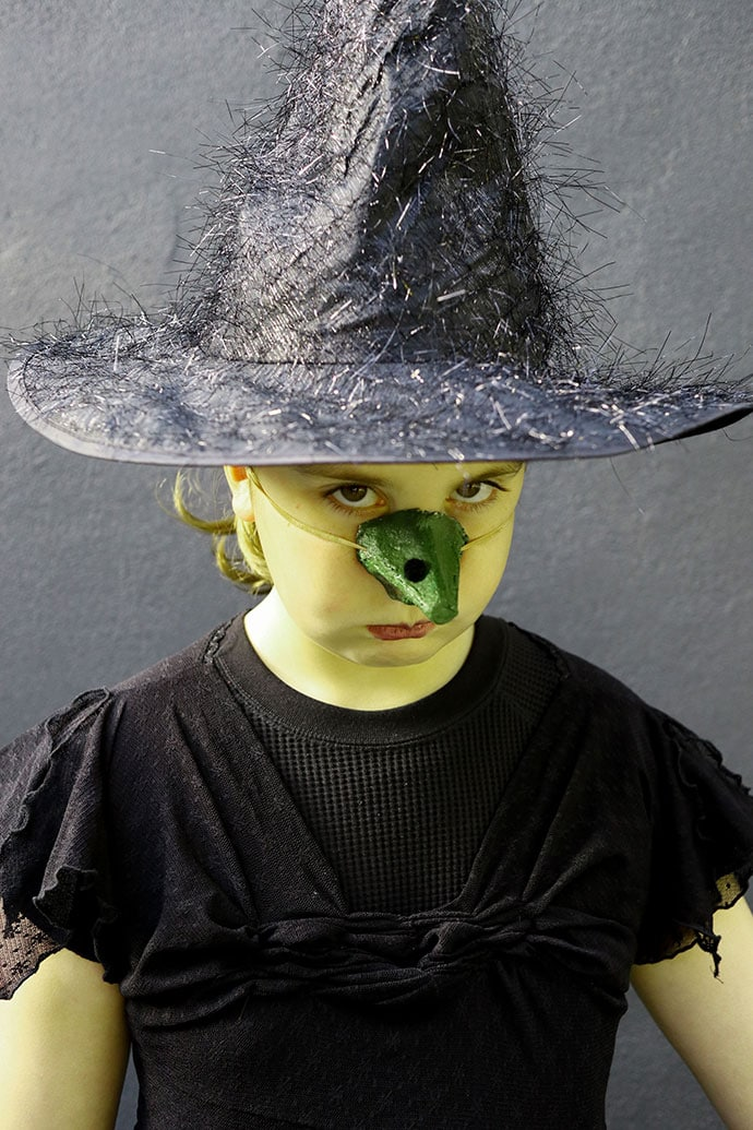 Girl with green face in witch costume