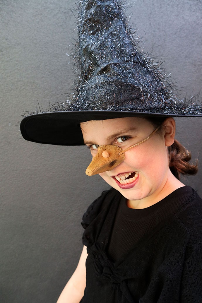 Girl wearing fake witch nose and black hat