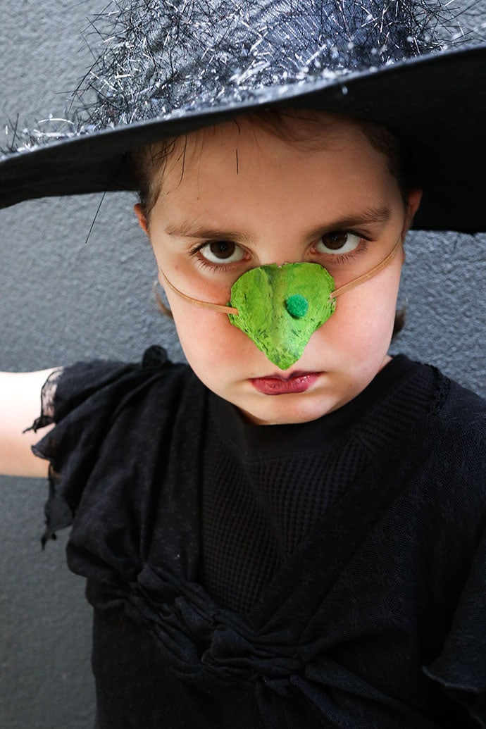 Girl wearing green witches nose