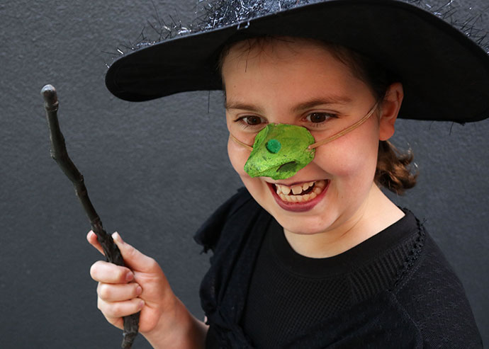 Girl wearing green witch nose
