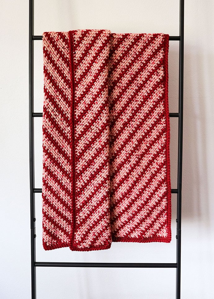 Candy stripes crochet blanket hanging on a ladder