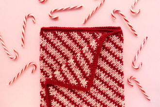 red and pink diagonal stripe blanket with candy canes