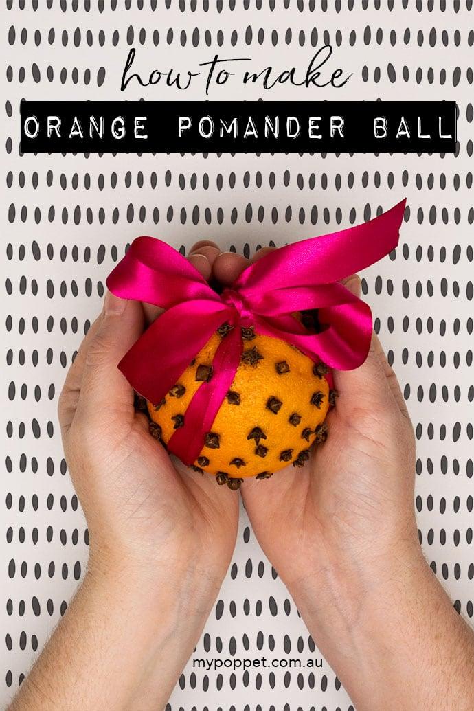 Hands holding orange pomander