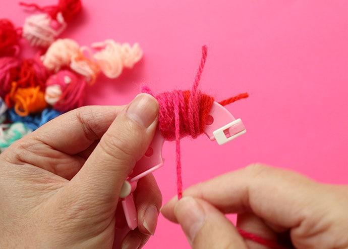 wrapping yarn around a pom pom maker