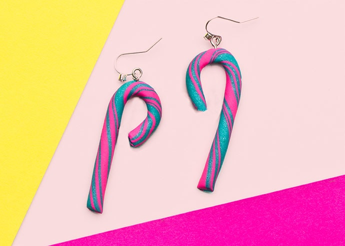 Candy cane earrings on pink background