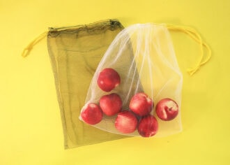 Mesh produce bags filled with fruit on yellow background