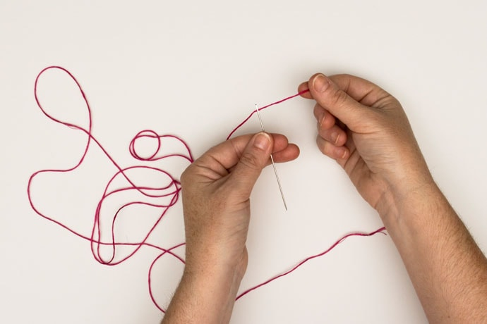 threading a needle with red thread
