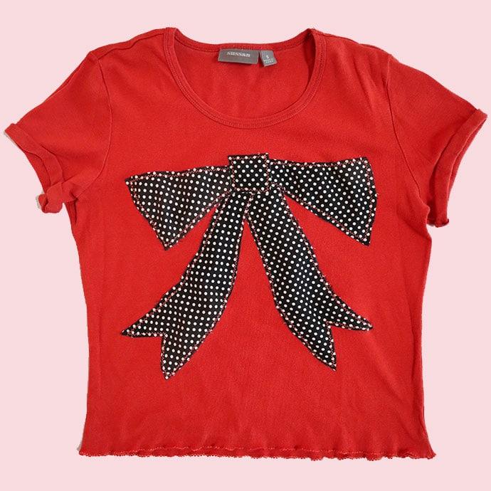 Orange t-shirt with black applique bow design