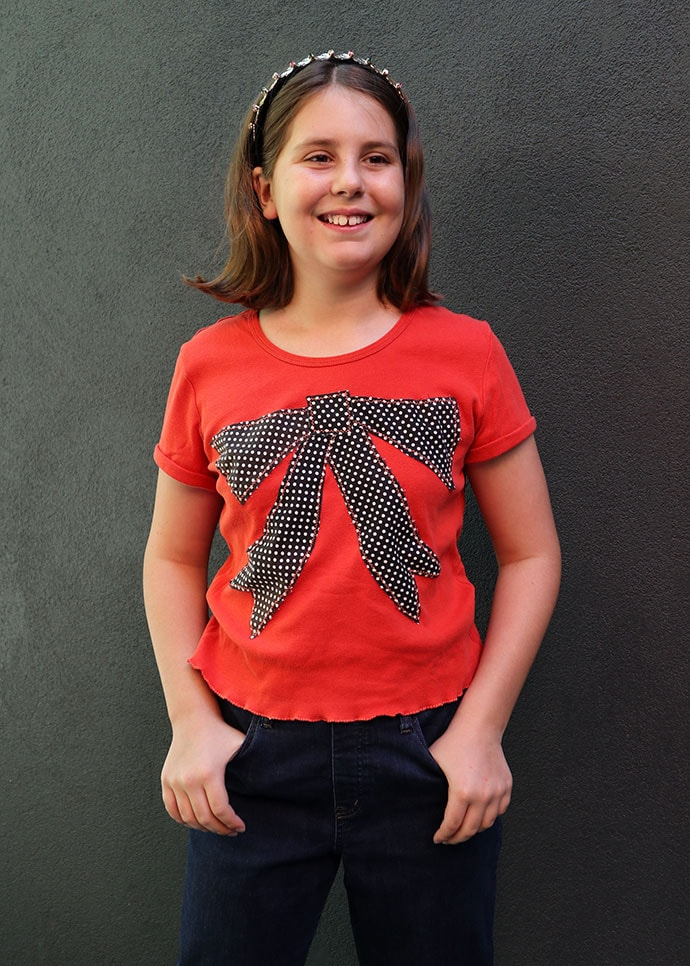 t shirt refashion idea - girl wearing and orange tshirt with large bow applique