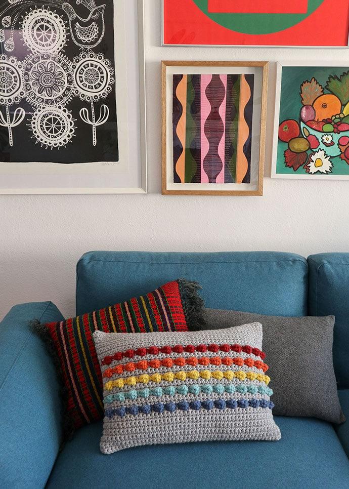 rainbow stripe crochet cushion on a blue sofa