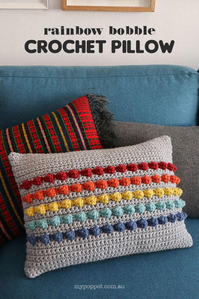 Rainbow bobble crochet cushion on blue sofa - crochet pillow pattern