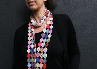 confetti scarf crochet pattern - woman wearing black and coloful crochet sacrf