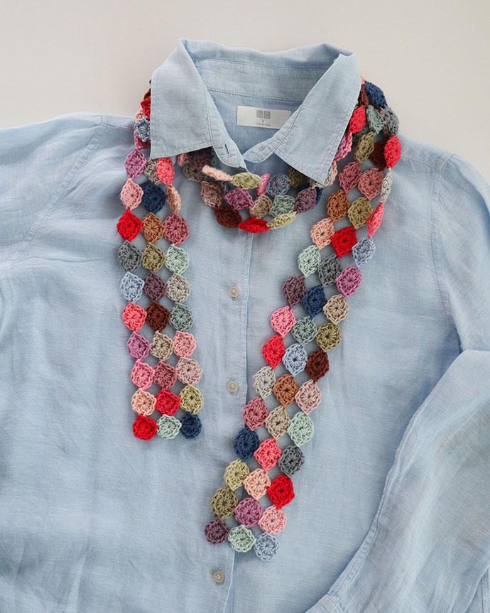 crochet scarf over light blue shirt