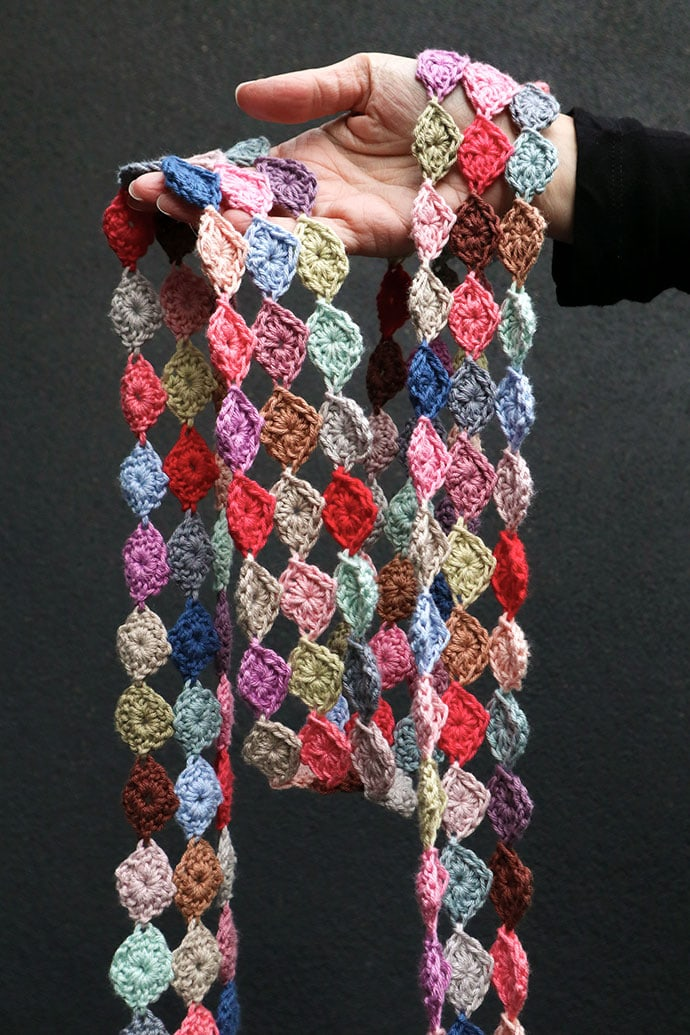 hand holding spotty crochet scarf