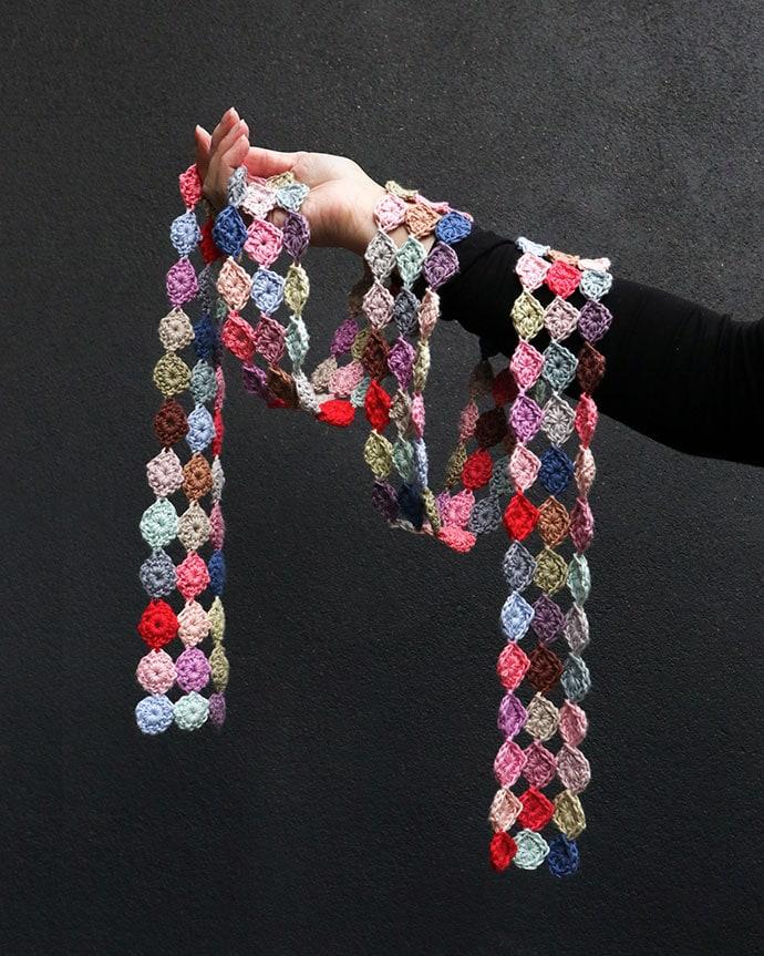 hand holding crochet scarf on black background