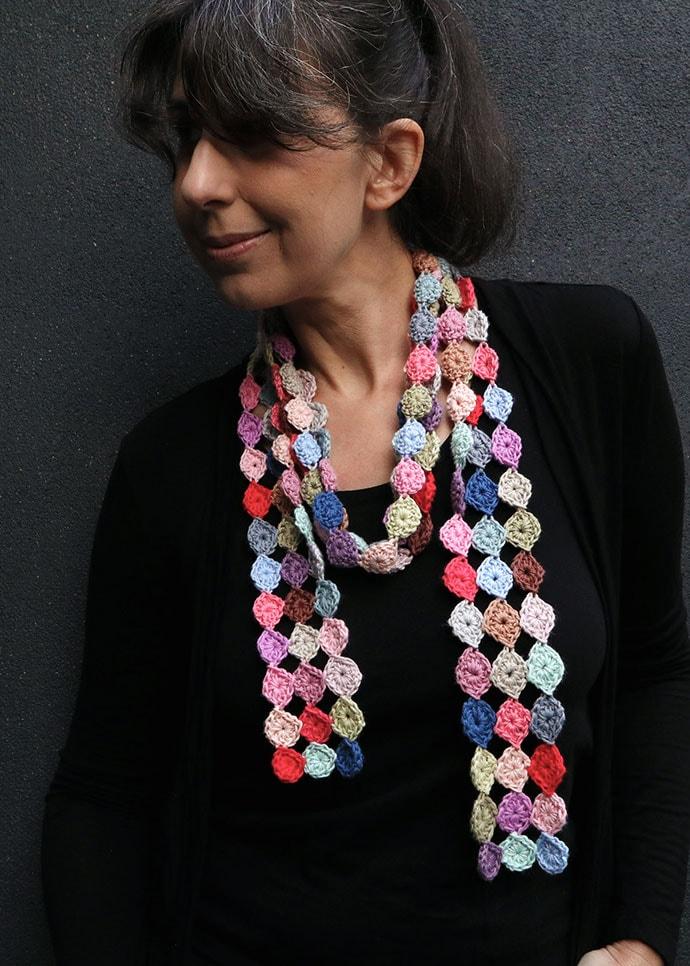 confetti scarf corchet pattern - woman dressed in black wearing spotty crochet scarf