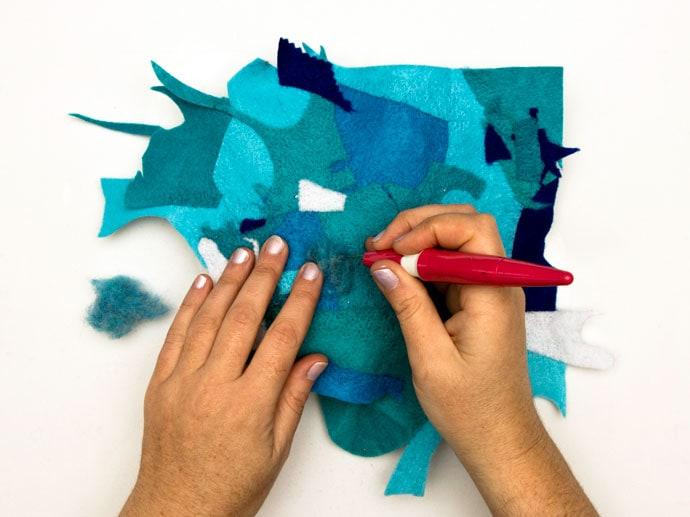 hands using needle felt tools to felt together scrap felt pieces