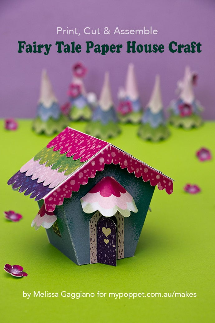 miniature paper house model on green background