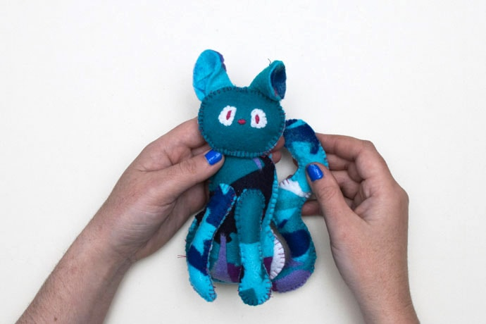 hands holding a patchwork felt cat
