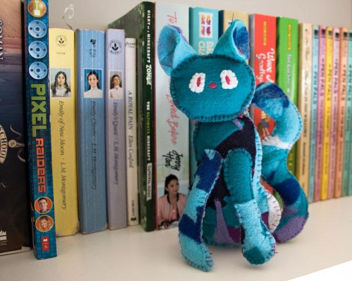handmade felt cat sitting on a bookshelf
