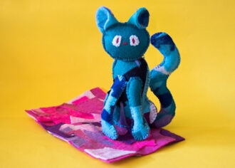 blue patchwork cat doll on pink mat