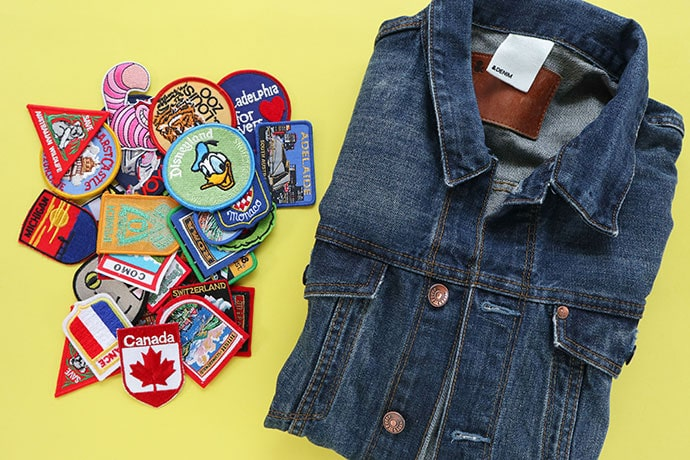 denim jacket next to a pile of embroidered patches