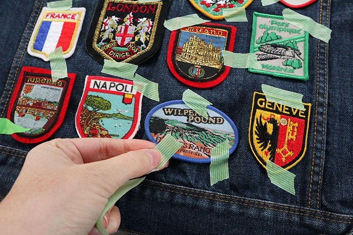 laying out patch design on denim jacket