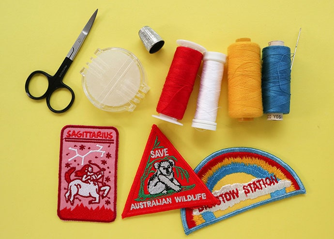 Sew on patches, thread bobbins, scissors and thimble on a yellow background