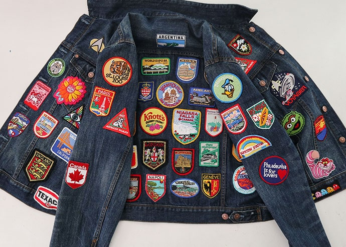 mens Denim jacket covered in vintage travel patches