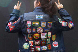 woman wearing denim jacket back covered in vintage travel patches